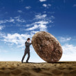 Businessman rolling a giant stone — Stock Photo #7973585