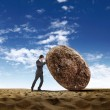 Businessman rolling a giant stone - Photo
