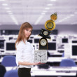 Businesswoman in office holding clock pyramid - Stok fotoğraf