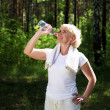 Stock Photo: Elderly womafter exercising in forest