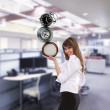 Businesswoman in office holding clock pyramid - Stock Photo