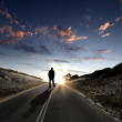 Man walking away at dawn along road — Stok fotoğraf