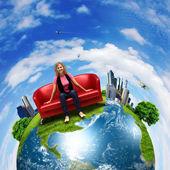 Młoda kobieta siedzi na kanapie natura tło — Zdjęcie stockowe