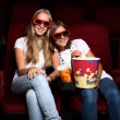 Two young girls watching in cinema — Stock Photo #8360358