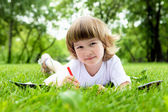 Portrait of little girl reading a book in the park — Stock Photo