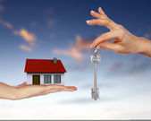 Human hands and house against blue sky — Stock Photo
