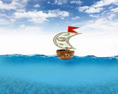 Nutshell ship with dollar banknote sail — Stock Photo