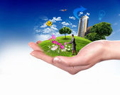 Human hand holding a green landscape — Stock Photo