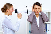 Young woman with megaphone in office — Stock Photo