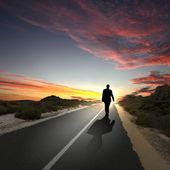 Man går bort i gryningen längs vägen — Stockfoto