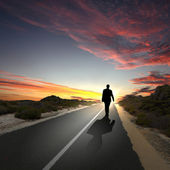 Man walking away at dawn along road — Stock fotografie