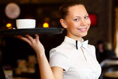 Portrait of young waitress holding a tray — Photo