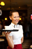 Portrait of young waitress holding a tray — Foto Stock