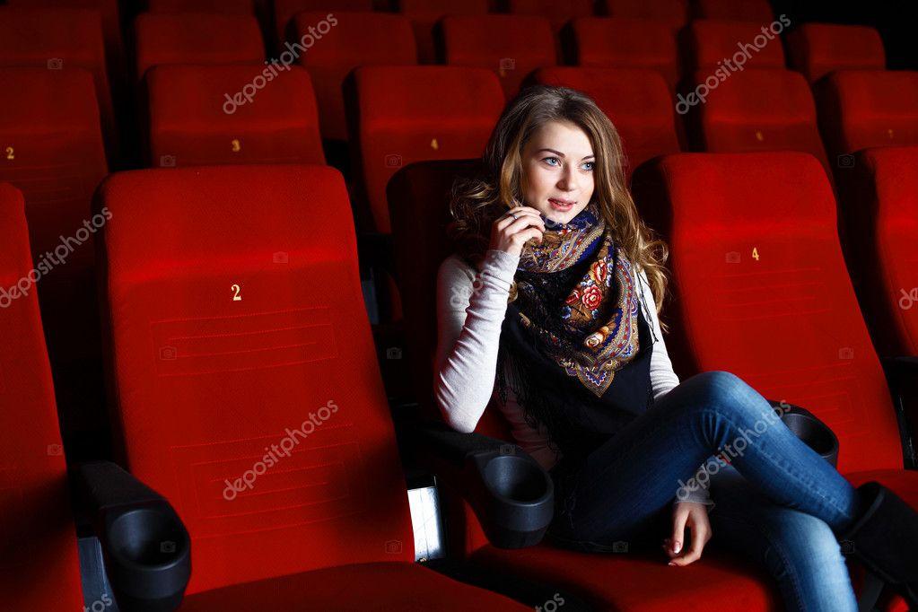 在电影院看电影的年轻女孩