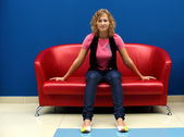 Young woman sitting on red sofa — ストック写真
