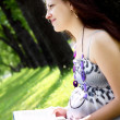 Portrait of pregnant woman in the park - Stockfoto