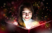 Young woman reading a magic book — Stock Photo