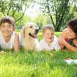 Stock Photo: Mother and her two sons in the park with a dog