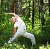 An elderly woman practices yoga — Stock Photo