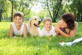 Matka a její dva synové v parku se psem — Stock fotografie