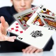 Young man showing poker cards - Stock Photo