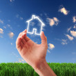 House and human hand against blue sky - Stock Photo