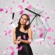 Stock Photo: Pretty woman under umbrella with petals around her