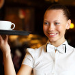 Royalty-Free Stock Photo: Portrait of young waitress holding a tray