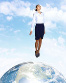 Young woman jumping and our planet earth — Stock Photo