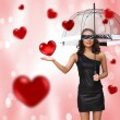 Pretty young woman with umbrella and hearts — Stock Photo #9317239