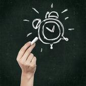 School blackboard and alarm clock symbol — Stock Photo