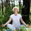 An elderly woman practices yoga - Stock Photo