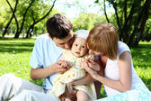 Young family together in the park — ストック写真
