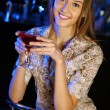Attractive woman in night club with a drink — Stock Photo #9398613