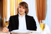 Young handsome man sitting in restaurant — Foto de Stock