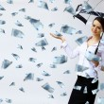 Business woman under money rain with umbrella — Stock Photo