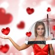 Stock Photo: Pretty young woman with umbrella and hearts