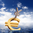 Currency symbols floating in blue sea - Stock Photo