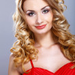 Young woman in red dress with curly hair — Stock Photo