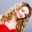 Young woman in red dress with curly hair — Stock Photo #9576393