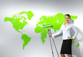 Businesswoman with paint brush and world map — Stock Photo