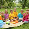 Group of children sitting together in the park — Stock Photo #9605750