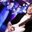 Young guitar player performing in night club — Stock Photo #9607133