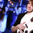 Young guitar player performing in night club — Stock Photo #9608888