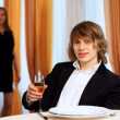 Young handsome man sitting in restaurant - Stockfoto