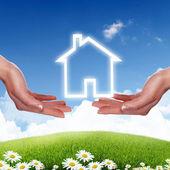 Hus och mänsklig hand mot blå himmel — Stockfoto