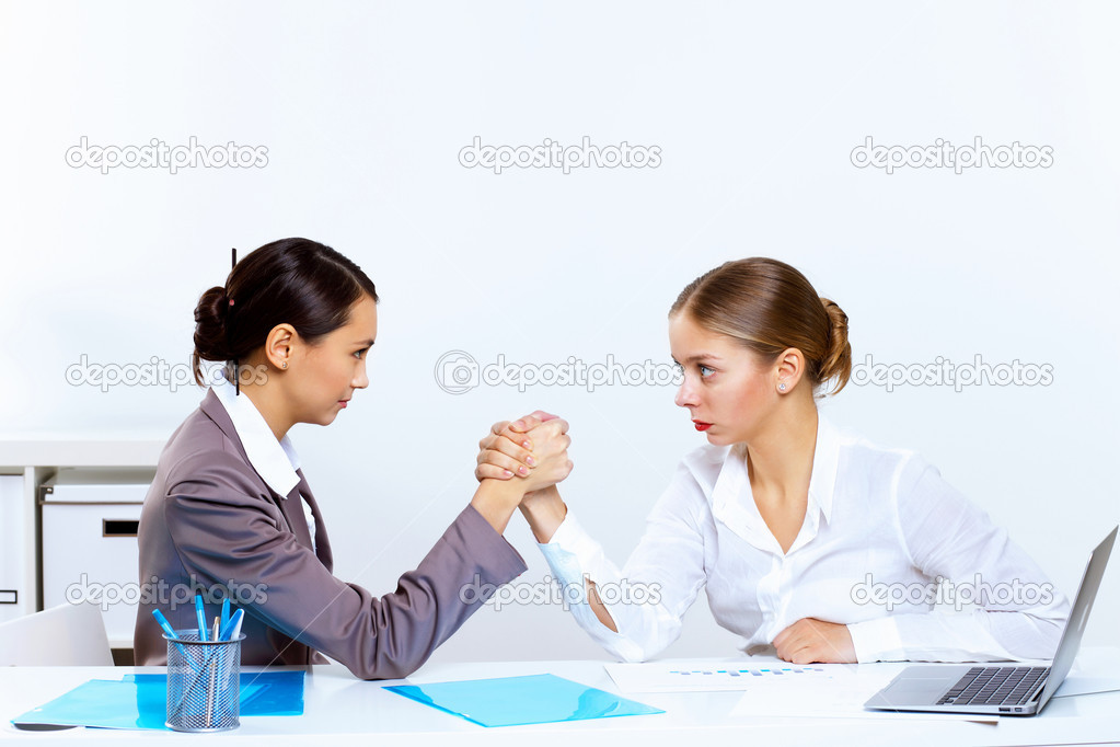 Two young women in business wear arm wrestling in office — Stock Photo #9634670