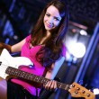 Young guitar player performing in night club — 图库照片