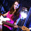 Young guitar player performing in night club — Stock fotografie