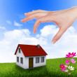 House and human hand against blue sky — Foto Stock